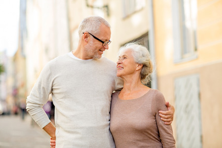 family, age, tourism, travel and people concept - senior couple hugging on city street photo