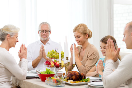 familia orando: concepto de familia, las vacaciones, la generación y la gente - sonriendo familia cenando y orando en casa