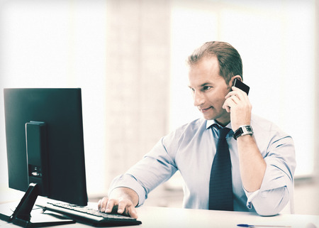 telephone call: picture of smiling businessman with smartphone in office Stock Photo