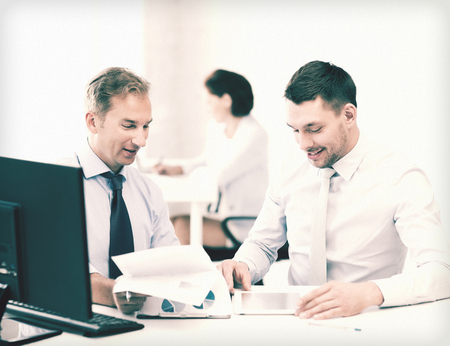 accountancy: businessmen with notebook and tablet pc discussing graphs on meeting Stock Photo