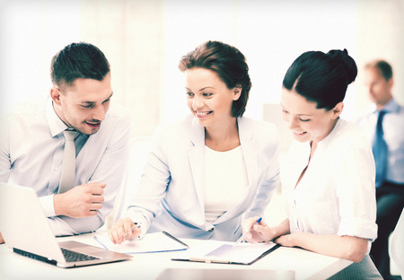 accountancy: smiling business team discussing something in office