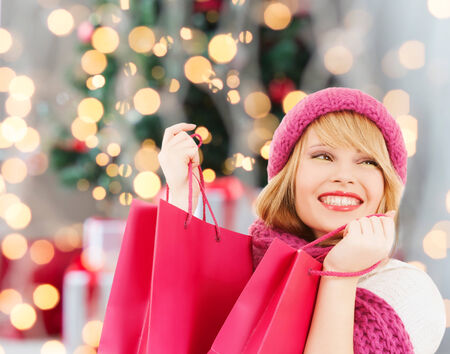 happiness, winter holidays and people concept - smiling young woman in hat and scarf with pink shopping bags over christmas tree background photo