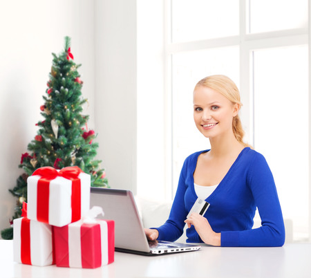 christmas, holidays, technology and shopping concept - smiling woman gift boxes, credit card and laptop computer over living room with christmas tree background photo