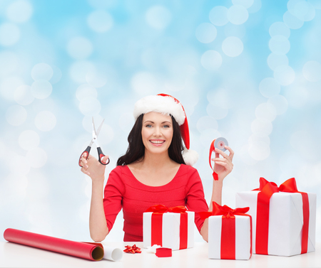 christmas, holidays, celebration, decoration and people concept - smiling woman in santa helper hat with scissors packing gift boxes over blue lights background photo