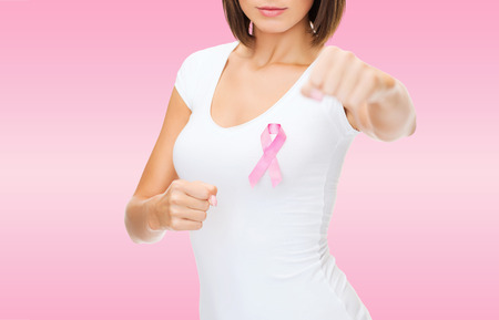 fighting cancer: healthcare and medicine concept - close up smiling young woman in blank white t-shirt with pink breast cancer awareness ribbon fighting over pink background