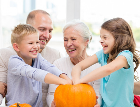 family, happiness, generation, holidays and people concept - happy family making halloween pumpkins at home photo