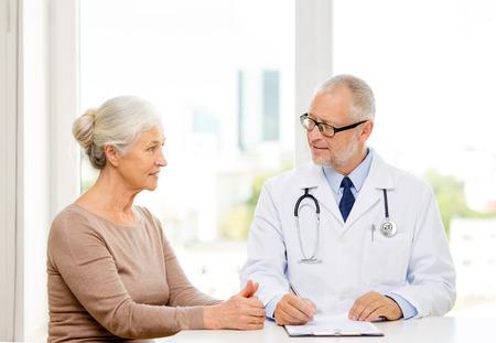 의학, 나이, 건강 관리 및 사람들이 개념 - 웃는 수석 여자와 의사 의료 사무실에서 회의