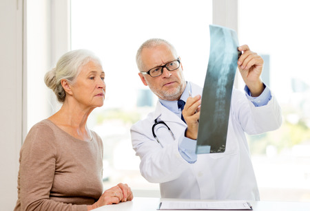 roentgen: medicine, age, health care and people concept - senior woman and doctor meeting in medical office