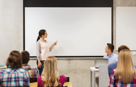 education, high school, technology and people concept - smiling student girl with remote control, laptop computer standing in front of white board and teacher in classroom Stock Photo