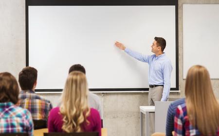 onderwijs, middelbare school, teamwork en mensen concept - lachende leraar staan in de voorkant van de studenten en het tonen van iets op witte boord in de klas