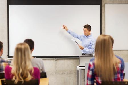 La educación, la escuela secundaria, la tecnología y el concepto de la gente - profesor con el bloc de notas, computadora portátil que se coloca delante de los estudiantes y que muestra algo en la pizarra en el aula Foto de archivo - 32106083
