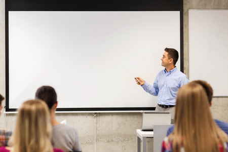 education, high school, technology and people concept - smiling teacher standing with remote control, laptop computer in front of white board and students in classroom