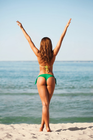 woman back view: summer vacation, holidays and people concept - young woman sunbathing on beach Stock Photo
