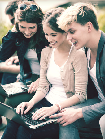 summer, internet, education, campus and teenage concept - group of students or teenagers with laptop computers hanging out Stock Photo