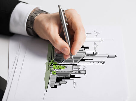building plans: business, marketing, planning and people concept - close up of male hand with pen drawing city on white paper