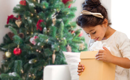 thankful: holidays, presents, childhood and people concept - smiling little girl with gift box over living room and christmas thee background