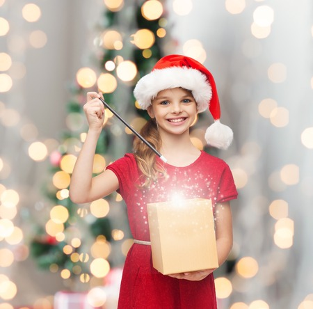 christmas, holidays, happiness and people concept - smiling girl in santa helper hat with gift box and magic wand over living room and christmas tree background photo