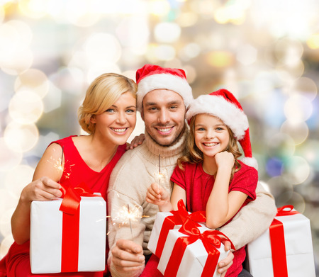 christmas, holidays, family and people concept - happy mother, father and little girl in santa helper hats with gift boxes over lights background