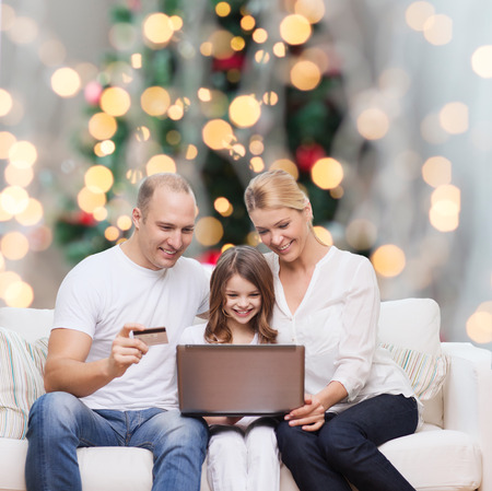 family, holidays, shopping, technology and people concept - happy family with laptop computer and credit card over christmas lights tree background photo
