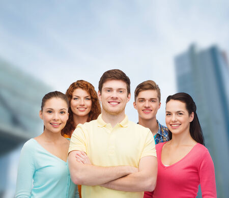 attractive man: friendship, city life, business and people concept - group of smiling teenagers over city background