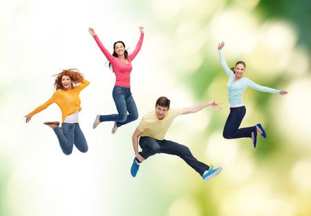 le bonheur, la liberté, l'écologie, l'amitié et les gens notion - groupe d'adolescents souriants sautant dans l'air sur fond vert