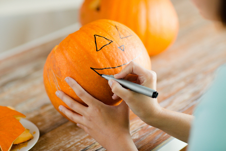 jackolantern: holidays, halloween, decoration and people concept - close up of woman with pumpkins at home Stock Photo