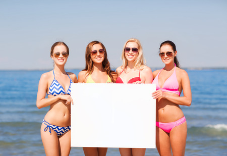 summer vacation, holidays, travel, advertising and people concept - group of smiling young women with big white blank billboard on beach photo