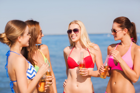 summer vacation, holidays, travel and people concept - group of smiling young women sunbathing and drinking on beach photo