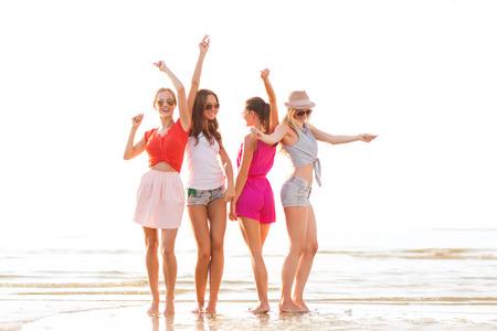Sommerferien, Urlaub, Reisen und Menschen Konzept - Gruppe von lächelnde junge Frauen mit Sonnenbrille und Freizeitkleidung tanzen am Strand Standard-Bild - 32282404