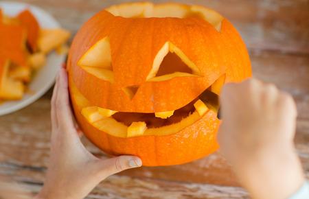 calabazas de halloween: d�as de fiesta, halloween, decoraci�n y concepto de la gente - cerca de la mujer con las calabazas en el hogar Foto de archivo