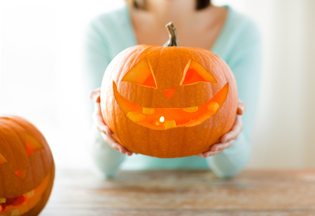 carved pumpkin: holidays, halloween, decoration and people concept - close up of woman with pumpkins at home Stock Photo