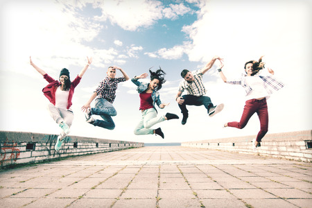 dancing girl: summer, sport, dancing and teenage lifestyle concept - group of teenagers jumping Stock Photo