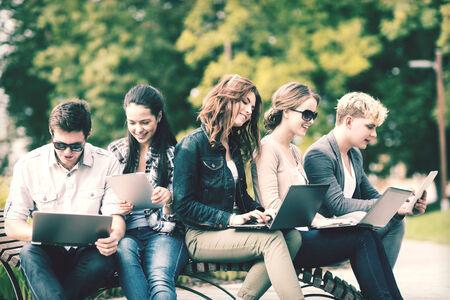 vysoká škola: léto, internet, vzdělání, školní areál a dospívající pojetí - skupina studentů a teenagery s notebookem a tabletové počítače visí ven Reklamní fotografie
