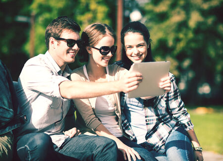 people having fun: summer, internet, social networking and teenage concept - group of teenagers taking photo with tablet pc outside