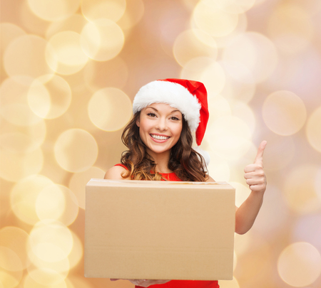 approvement: christmas, winter holidays, delivery, gesture and people concept - smiling woman in santa helper hat with parcel box showing thumbs up over beige lights background