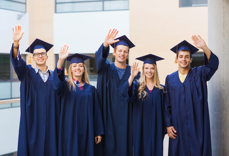 education, graduation and people concept - group of smiling students in mortarboards and gowns waving hands outdoors photo