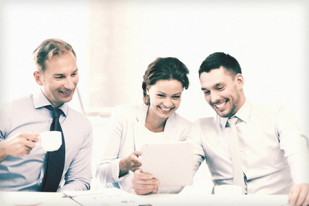 having a break: happy business team having fun with tablet pc in office Stock Photo