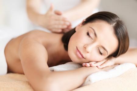 la salud, la belleza, la estación y el concepto de relajación - hermosa mujer con los ojos cerrados en el salón de spa recibiendo masaje Foto de archivo