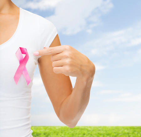 fighting cancer: healthcare, people, charity and medicine concept - close up of woman in t-shirt with pink breast cancer awareness ribbon over blue sky and grass background Stock Photo