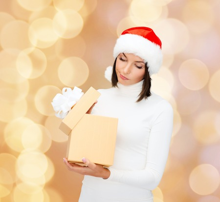 christmas, winter, happiness, holidays and people concept - woman in santa helper hat with gift box over beige lights background photo