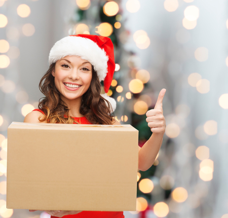 delivery room: christmas, winter holidays, delivery, gesture and people concept - smiling woman in santa helper hat with parcel box showing thumbs up over living room with christmas tree background