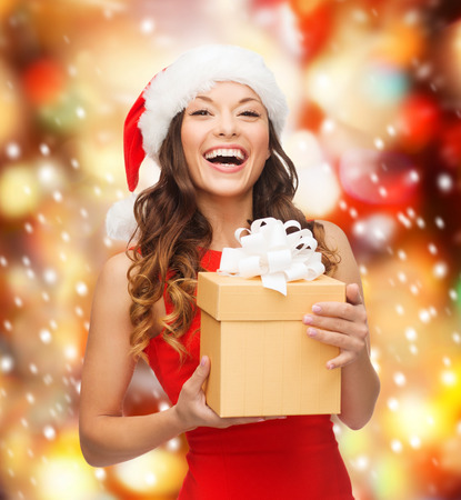 christmas, xmas, new year, happiness concept - laughing asian woman in santa helper hat with gift box photo