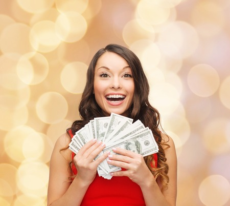 bargain: christmas, sale, banking, winning and holidays concept - smiling woman in red dress with us dollar money over beige lights background