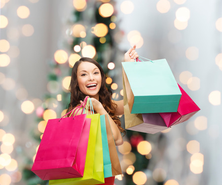 sale, gifts, holidays and people concept - smiling woman with colorful shopping bags over living room and christmas tree background photo