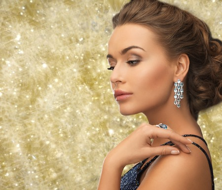 ear rings: people, holidays and glamour concept - beautiful woman in evening dress wearing ring and earrings over yellow lights background
