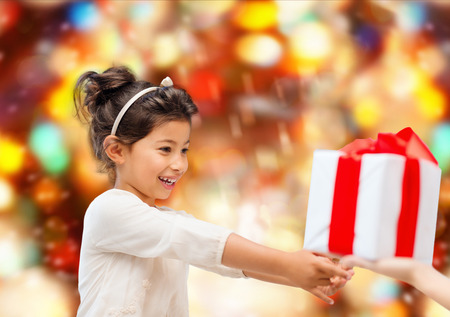 grateful: holidays, presents, christmas, childhood and people concept - smiling little girl with gift box over red lights background Stock Photo