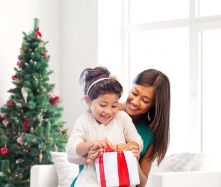 asian trees: holidays, celebration, family and people concept - happy mother and little girl with gift box over living room and christmas tree background