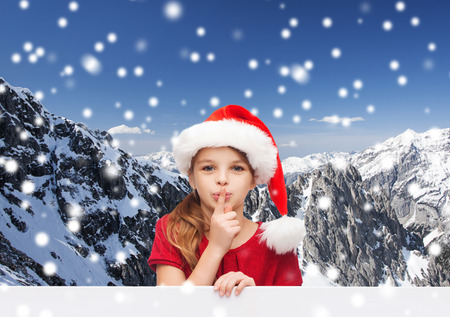 little finger: christmas, holidays, childhood and people concept - smiling little girl in santa helper hat with finger on her lips over snowy mountains background