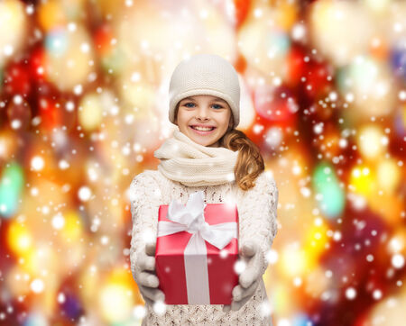 christmas, xmas, winter, happiness concept - smiling girl in hat, muffler and gloves with gift box photo