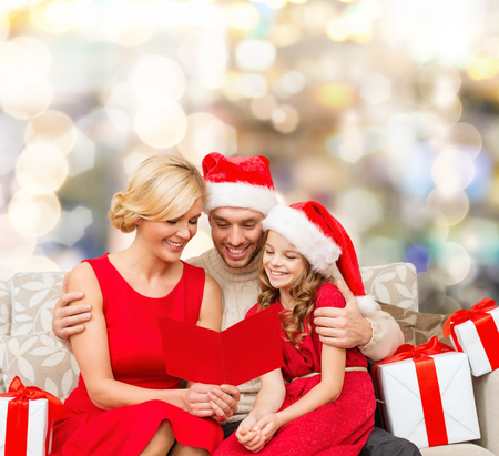 christmas, holidays,  family and people concept - happy mother, father and little girl in santa helper hats with gift boxes reading geeting card over lights background photo
